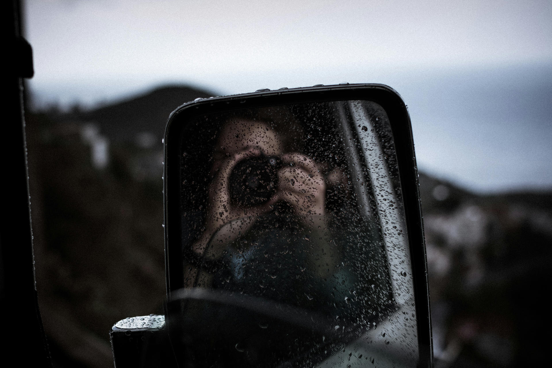 Photographing oneself in a rainy mirror.