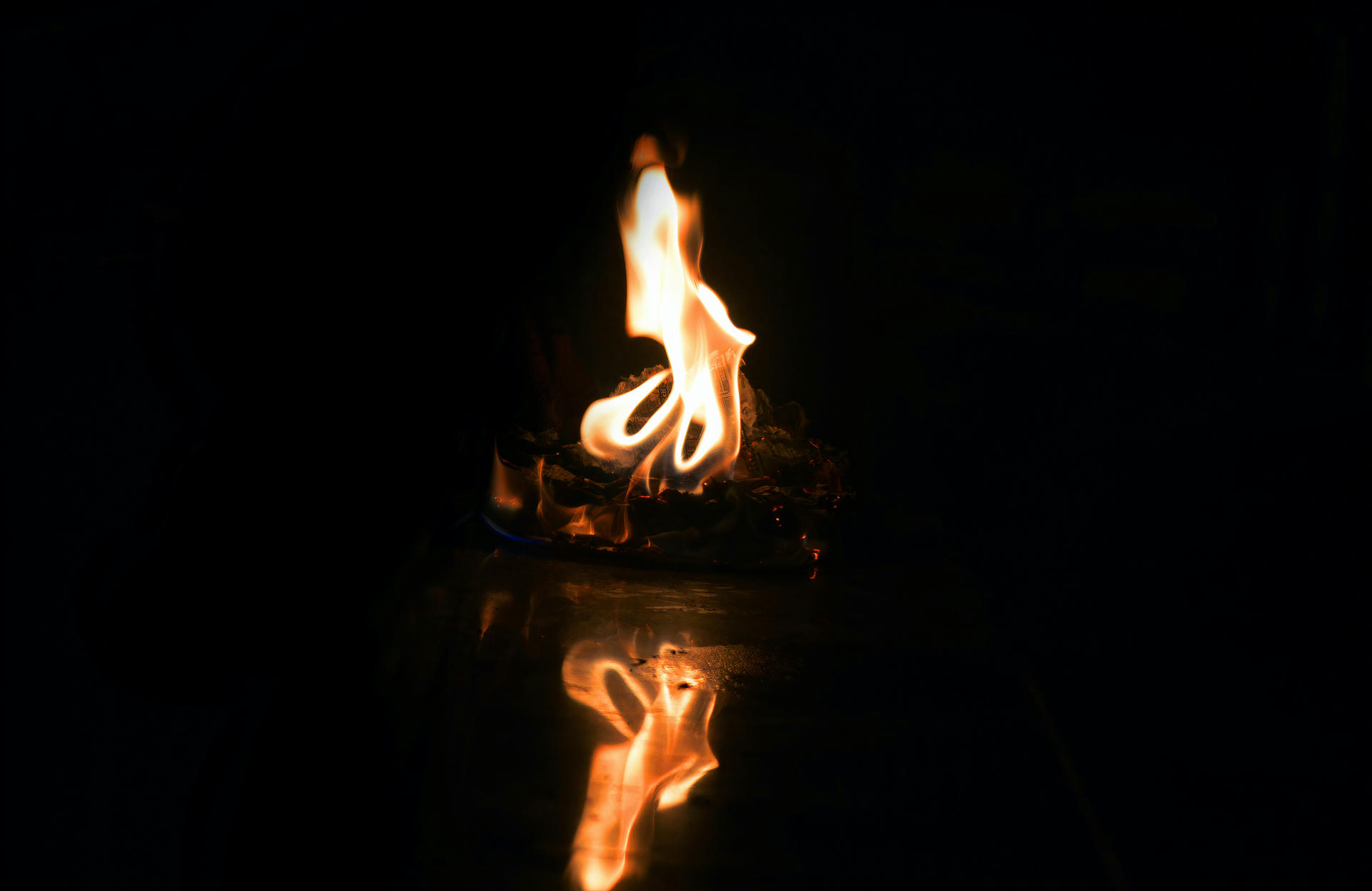 A flame with a reflection.